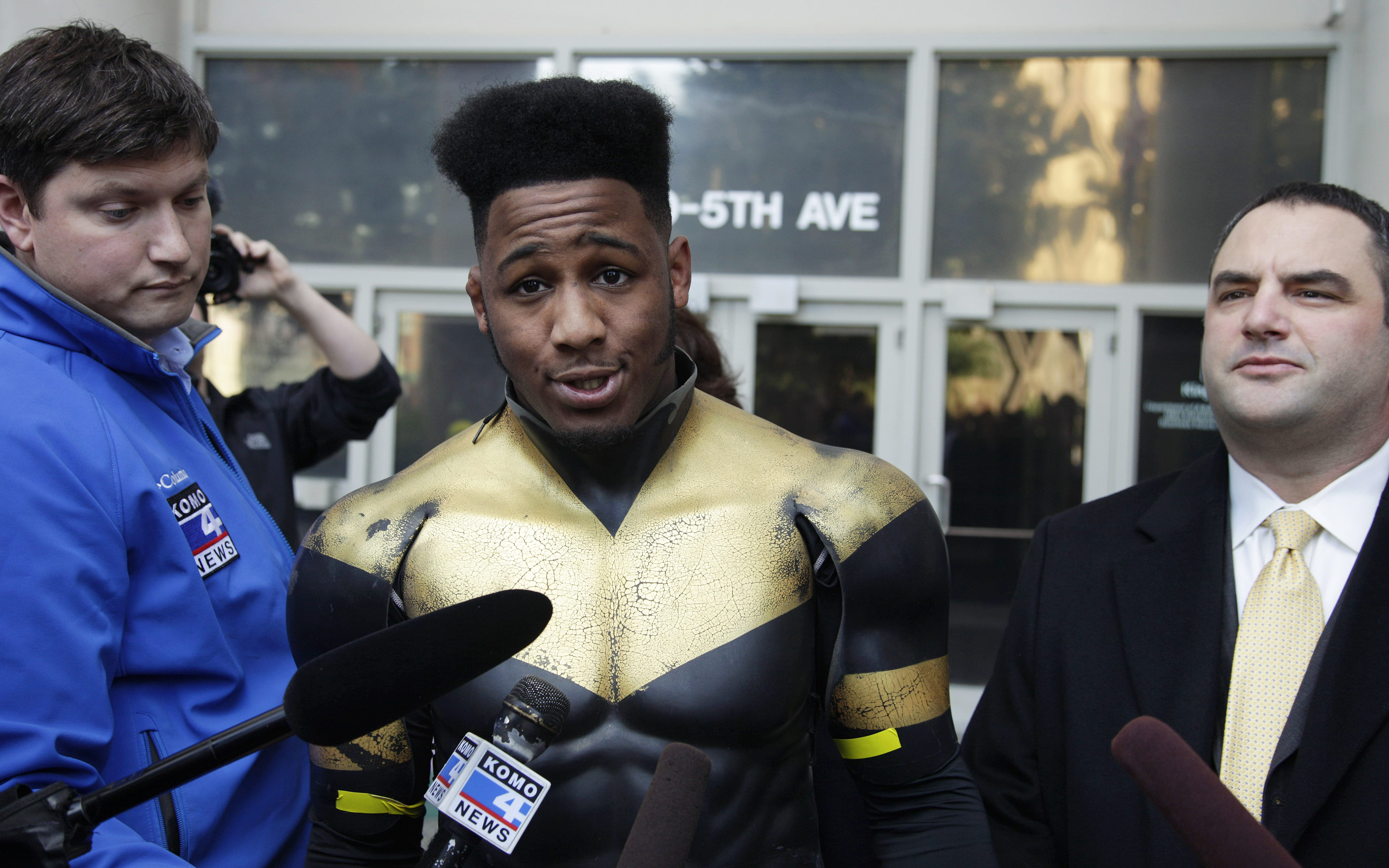 "Ben Fodor, a self-styled superhero who goes by the name ""Phoenix Jones,"" talks to reporters as he stands next to one of his attorneys, Matt Hartman, right, after Fodor appeared in court, Thursday, Oct. 13, 2011, in Seattle. Prosecutors have not yet filed charges  against Fodor after he was arrested Sunday after police say he pepper sprayed a group of people downtown as they left a nightclub. (AP Photo/Ted S. Warren)"