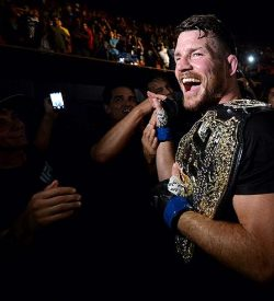 INGLEWOOD, CA - JUNE 04: Michael Bisping of England celebrates with his title belt after his first round knockout win against Luke Rockhold during the UFC 199 event at The Forum on June 4, 2016 in Inglewood, California. (Photo by Brandon Magnus/Zuffa LLC/Zuffa LLC via Getty Images)